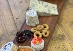 Een grote kaasplank samenstellen met kaas, antipasti, wijn, worst en chocolade